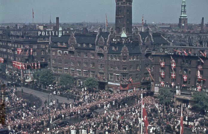 Den 12. maj 1945 er københavnerne på gaden for at hylde den britiske feltmarskal Montgomery, som kører i parade gennem den festklædte hovedstad. På dette farvefoto ses kortegen med feltmarskallen ved Rådhuspladsen i det nyligt befriede København. I artiklen her kan du finde interessante podcasts om Københavns historie. Jeg synes, listen mangler podcasts om besættelsestidens København. Kontakt mig meget gerne, hvis du kender til nogle, som du kan anbefale. Kilde til dette foto: Nationalmuseet, Danmark. Fotograf: Ukendt. Licens ifølge Nationalmuseet: No known rights.