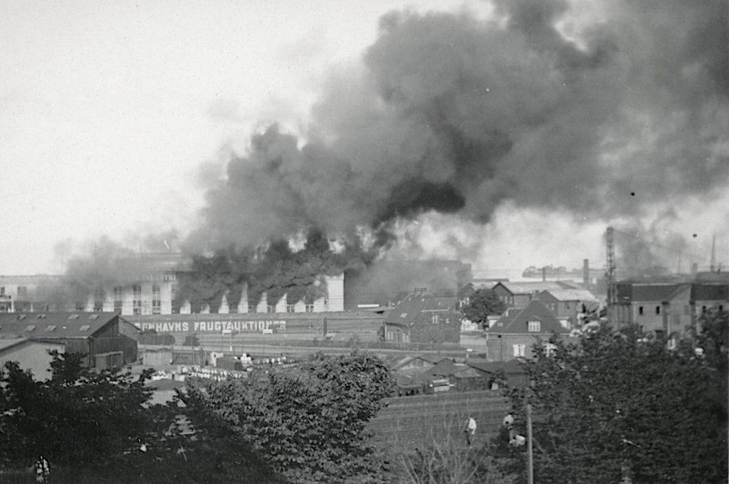 På billedet her kan du se brændende fabriksbygninger efter BOPAs angreb på Riffelsyndikatet den 22. juni 1944. Fotokilde: Nationalmuseet, Danmark. Fotograf: Ikke oplyst. Licens ifølge Nationalmuseet: No known rights.