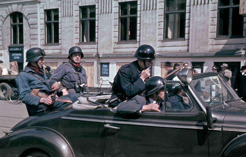 En gruppe modstandsfolk ses her i en bil på Nytorv i København i maj 1945. Fotokilde: Nationalmuseet, Danmark. Licens ifølge Nationalmuseet: No known rights. Fotograf/skaber: Formodentlig reklamefotograf Knud Rading.