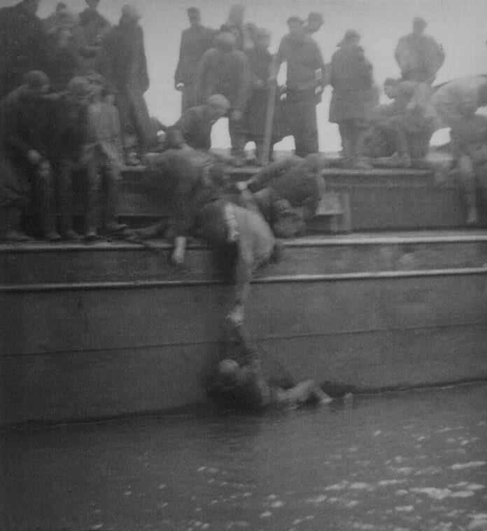 En KZ-fange bliver tilsyneladende hjulpet tilbage op på Skibet fra Helvede af en medfange. Fotokilde: Møns Lokalarkiv